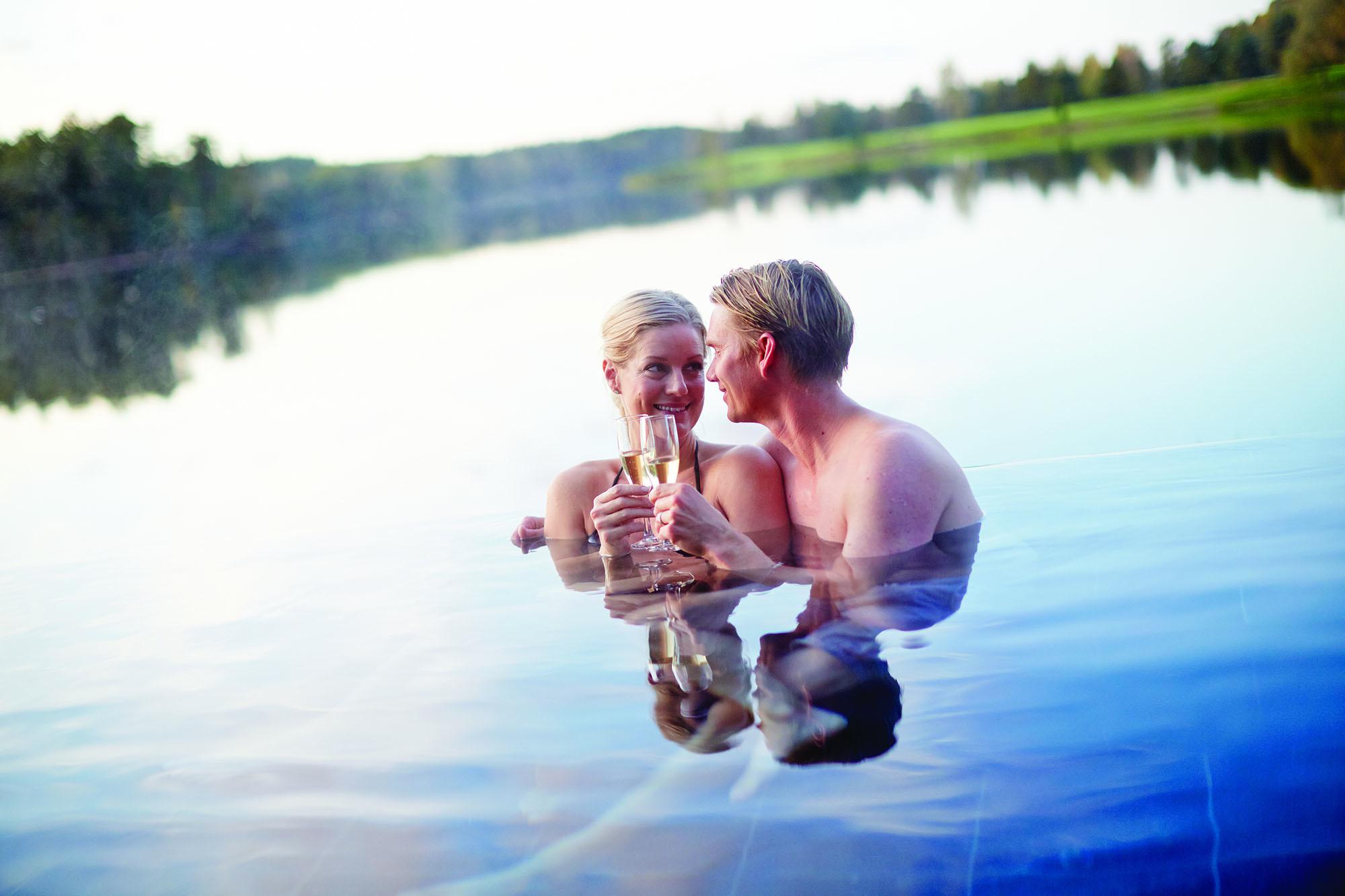 Ett par som badar och dricker champagne.