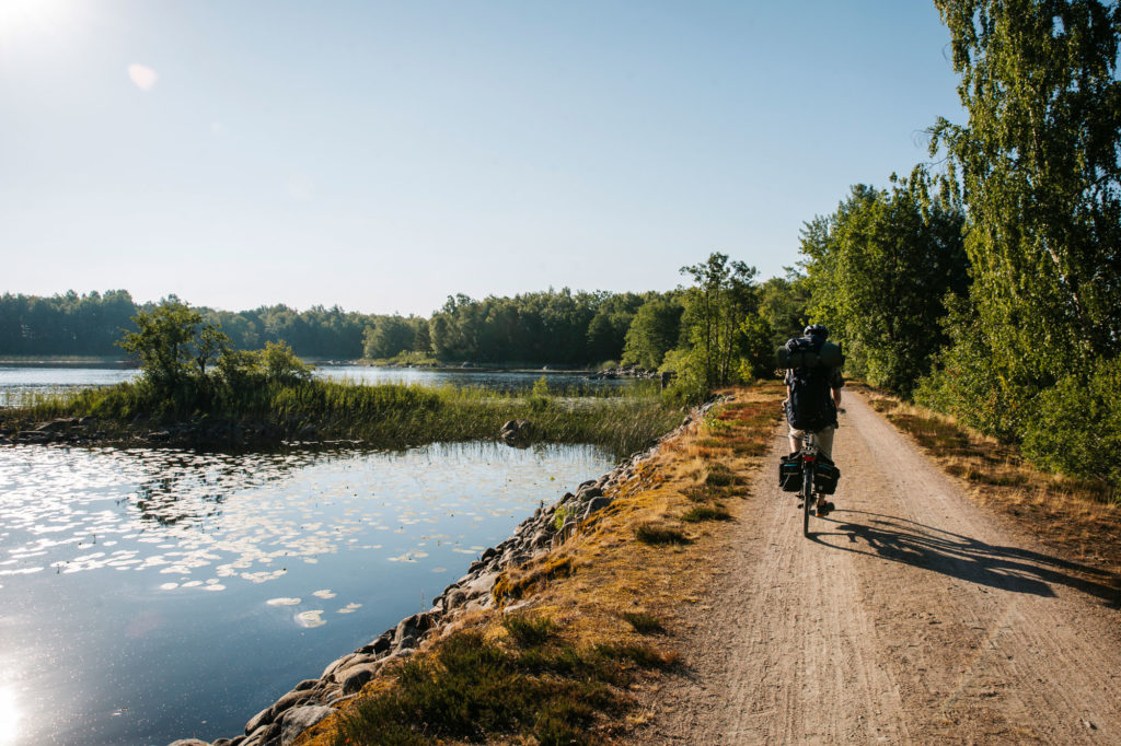 Man cyklar längs sjökanten i Åsnens nationalpark i Småland