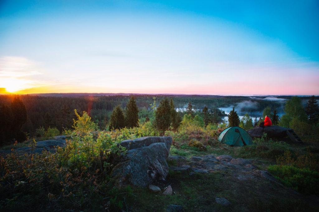 Människor tältar med fantastisk utsikt över en sjö i Småland