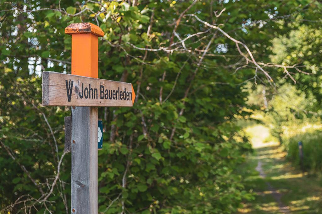 Skylt med texten John Bauerleden och orange färg som står i lummig buskage