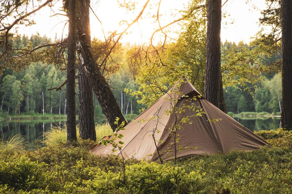 Brunt tält som står vid en sjö i solnedgången mitt bland blåbärsris