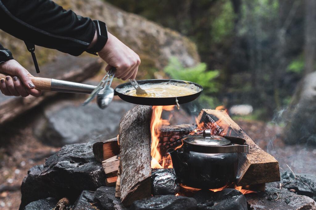 Alexander Stenfeldt rör en äggröra i en stekpanna över en öppen eld med en tekanna ståendes halvt i elden