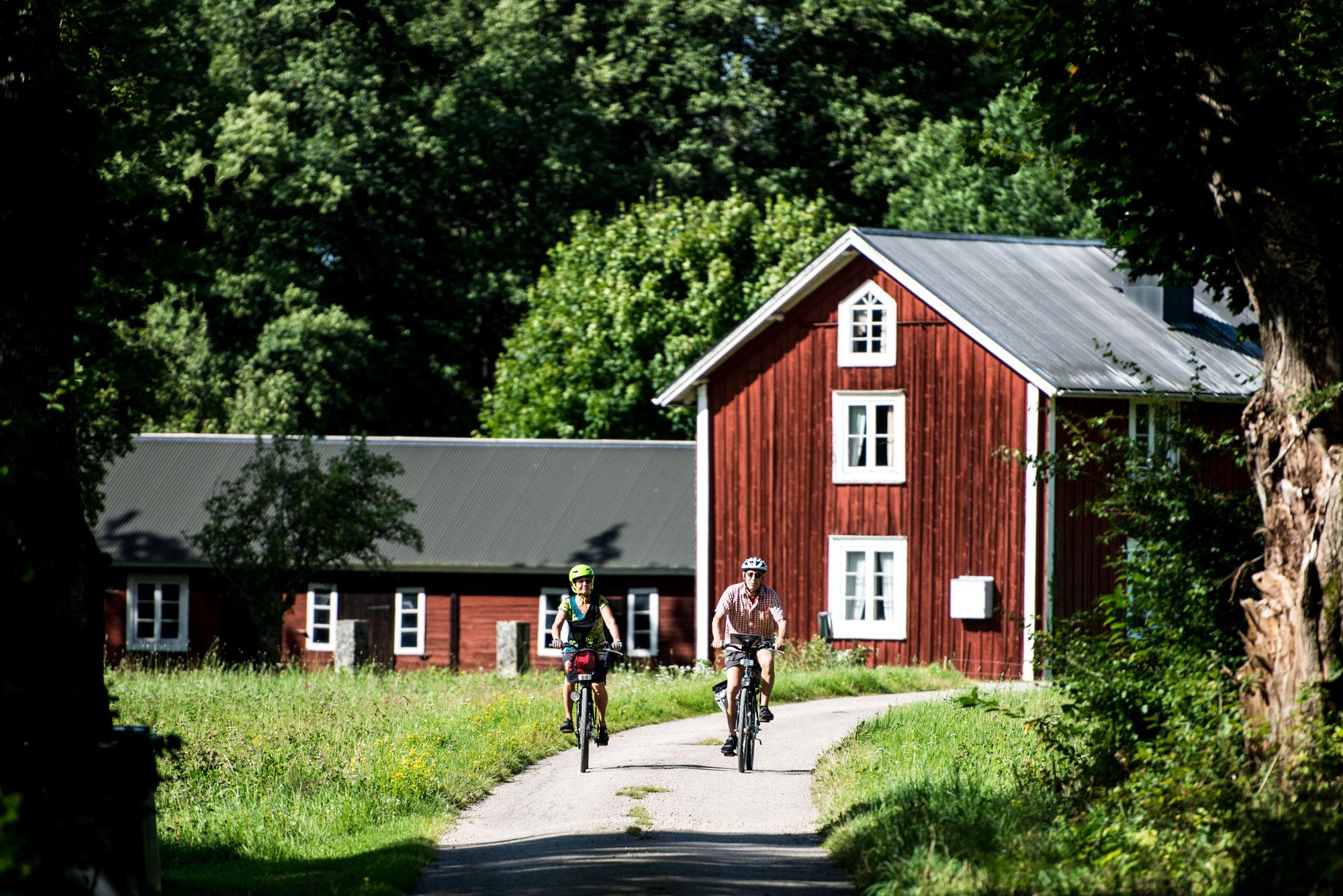 Par cyklar på väg förbi röda stugor på Utvandrarleden