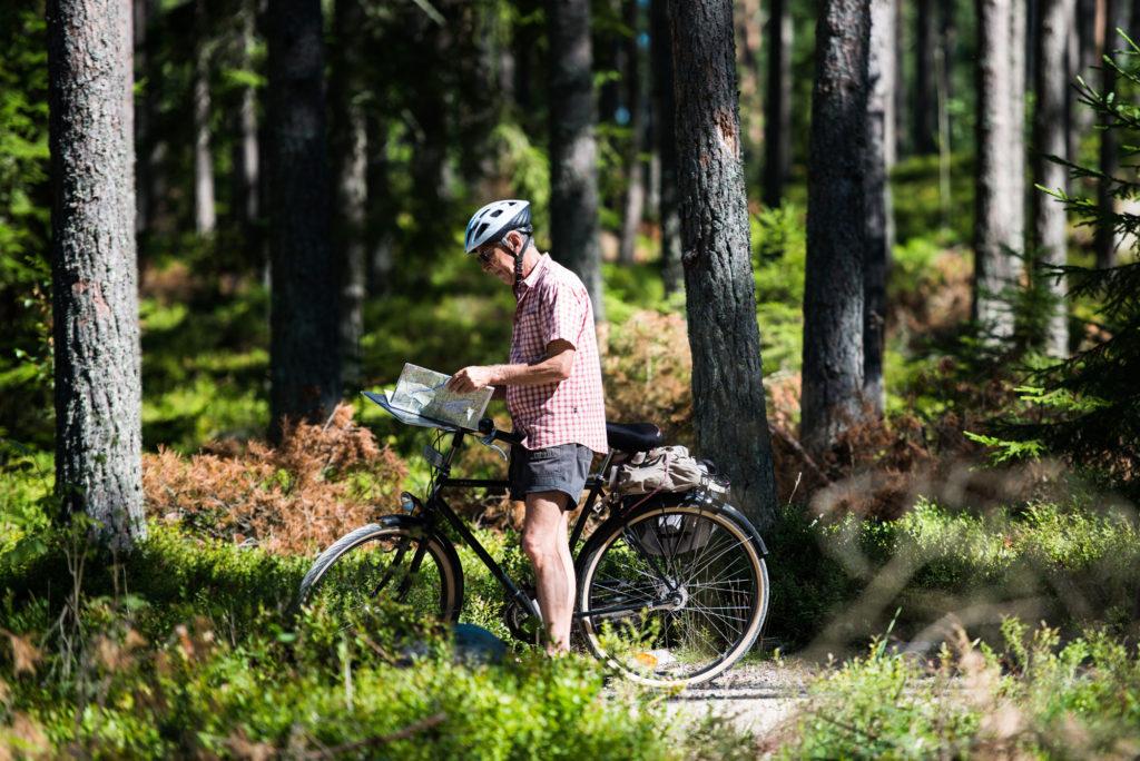 Man har stannat och tittar på sin karta över Utvandrarleden i Småland