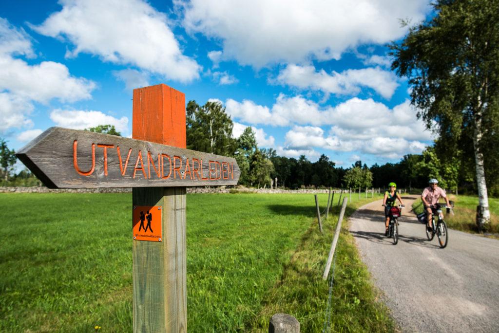 Par cyklar förbi skylt Utvandrarleden i Småland