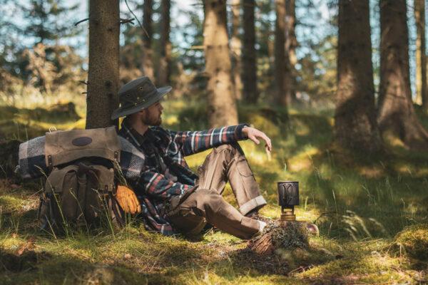 Alex Stenfeldt sitter lutad mot en tall i en småländsk skog med hatt och rutig skjorta på sig