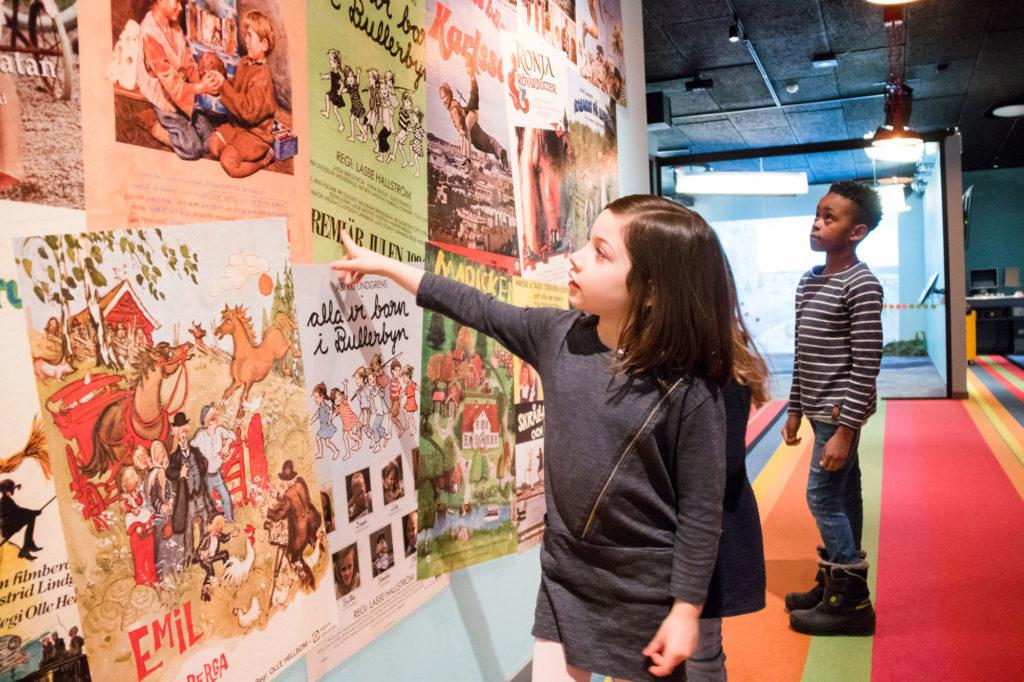 Barn i Filmbyn tittar nyfiket på postrar på en vägg