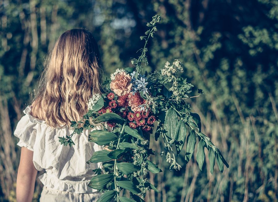 Kvinna håller i blommar vid Butik Botanik i Småland