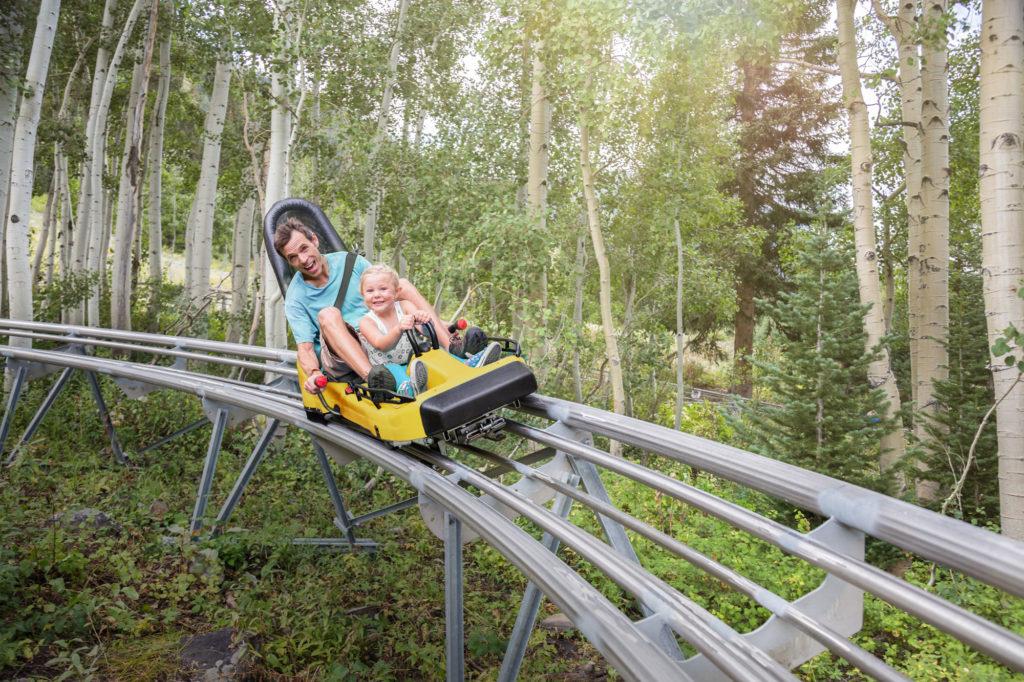 Pappa sitter i rodel med barn vid Isaberg Mountain Resort
