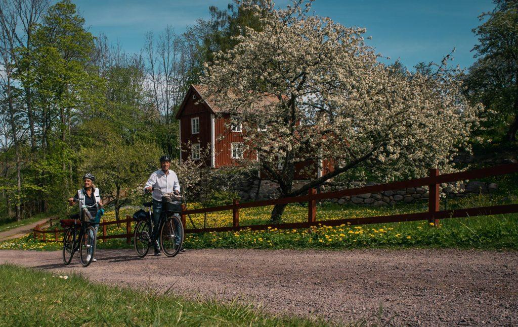 Man och kvinna cyklar i den gamla industribyn Röttle strax söder om Gränna