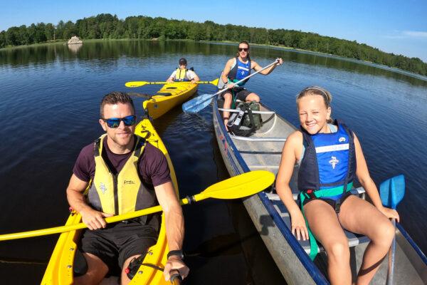 Team Lost med familj paddlar kajak på en småländsk sjö och tittar leende in i kameran med flytvästar på sig