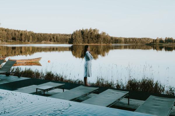 Kvinna i badrock tittar ut över insjö i Småland