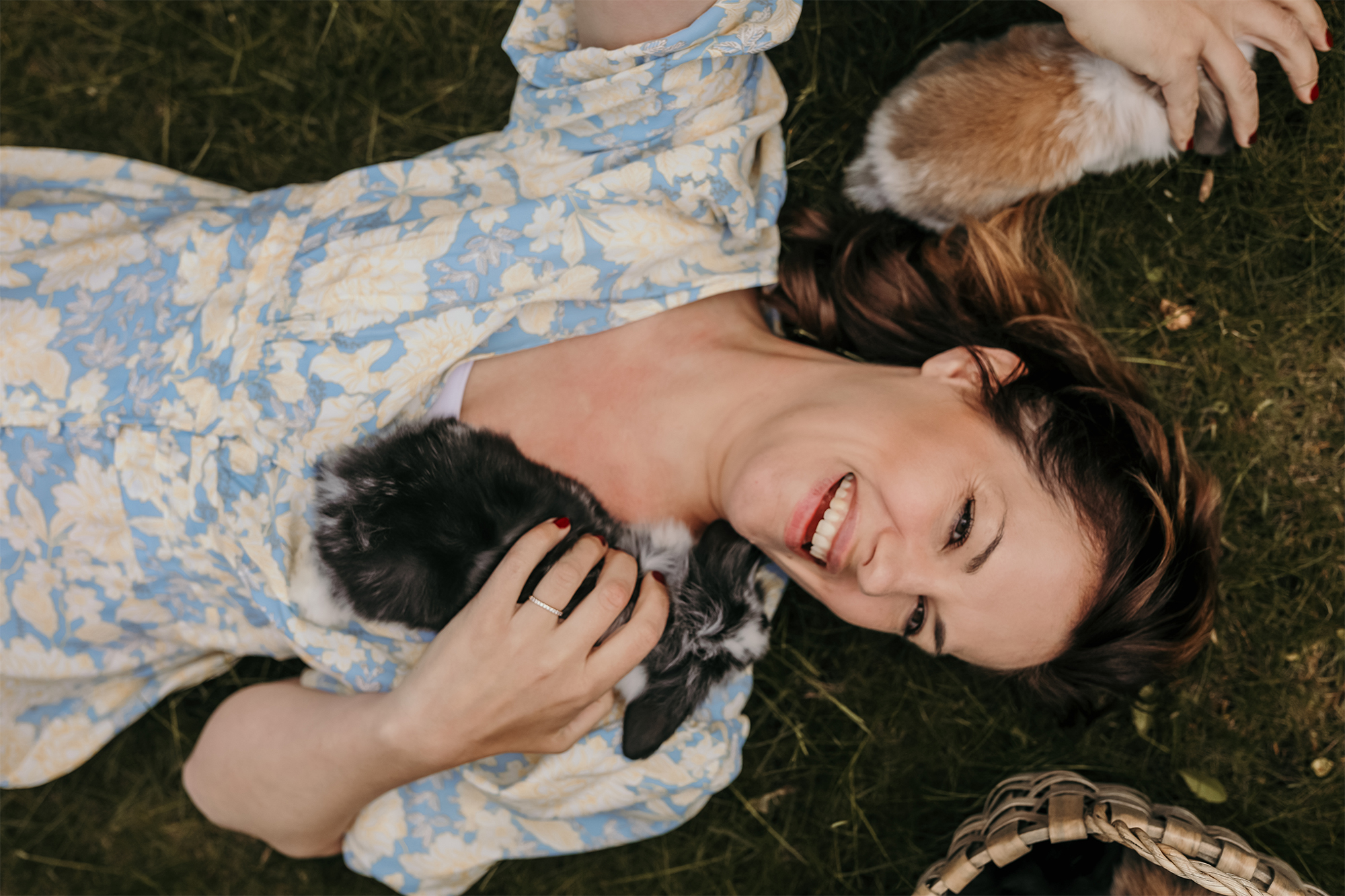 Emma Johansson ligger i gräset i en blommig klänning och myser med kaninungar