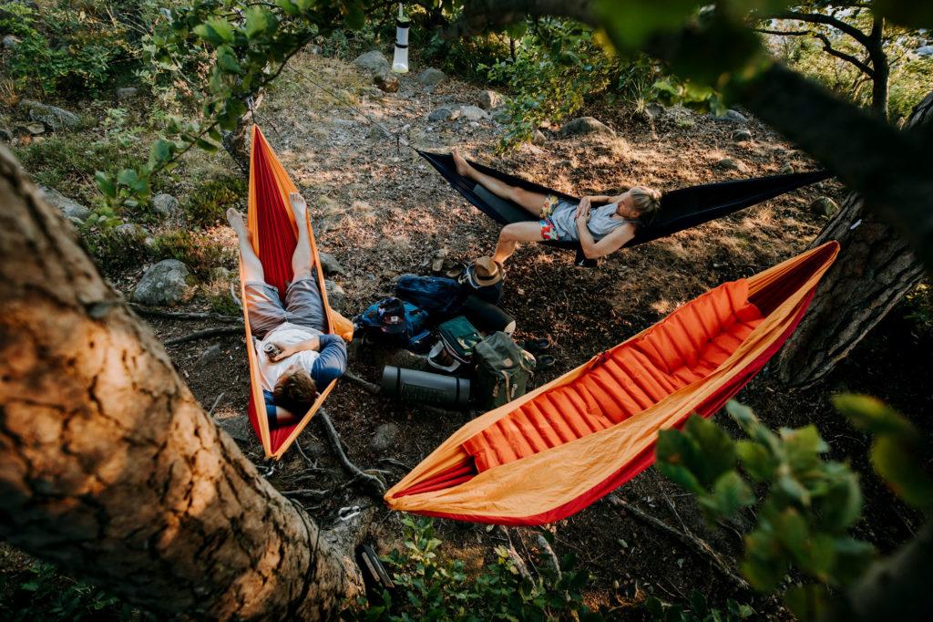 Två män ligger i hängmattor vid en vandringsled i Småland