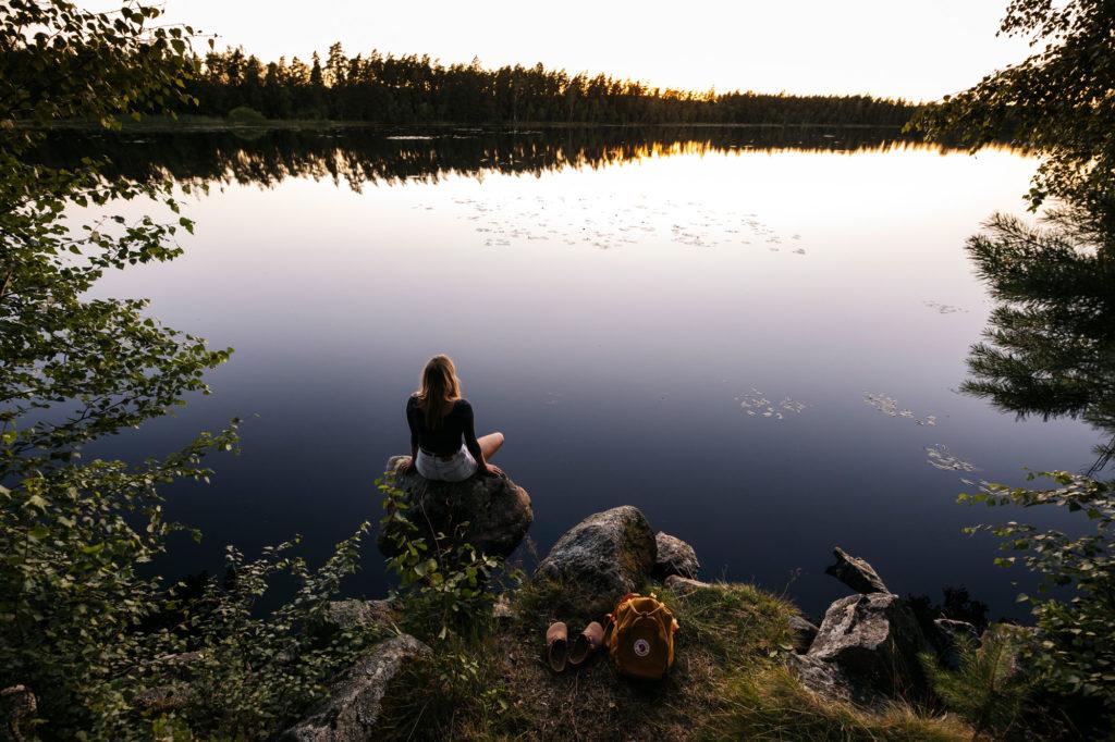 Kvinna kopplar av vid sjökanten i en av Smålands många nationalparker