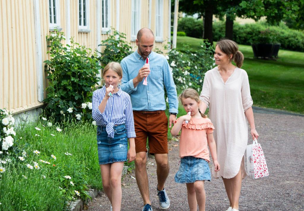 Familj äter polkagrisar i Gränna utanför Grenna Museum