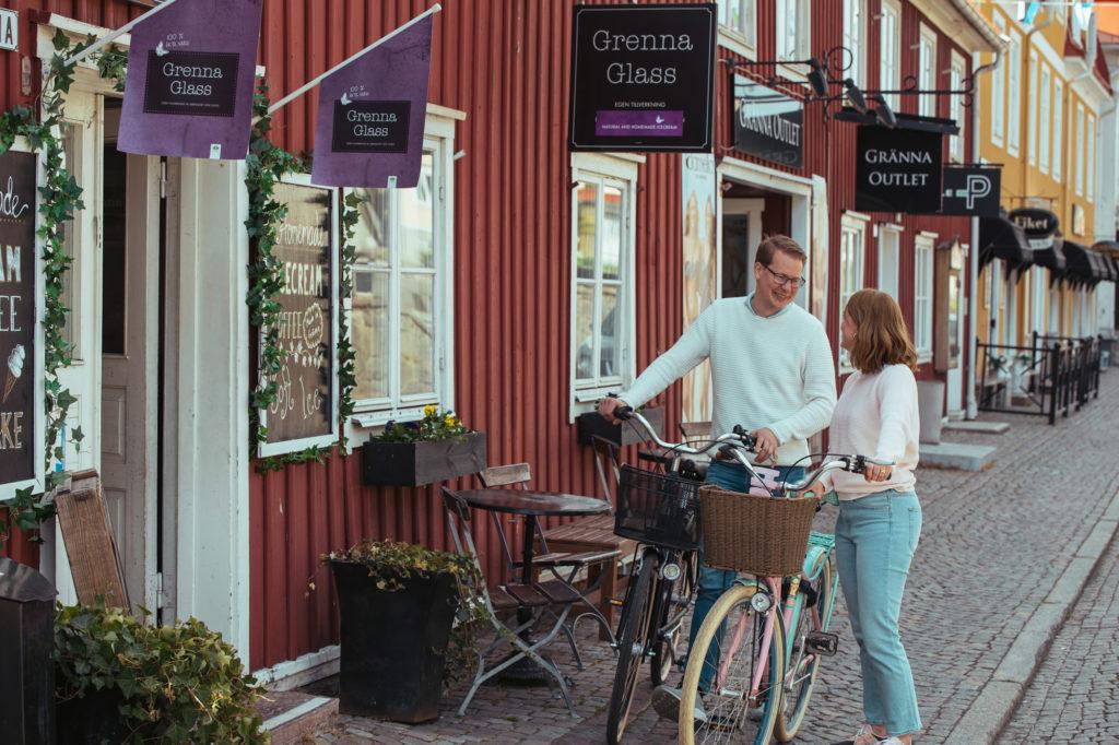Man och kvinna med cyklar utanför Grenna Glass på Brahegatan i Gränna