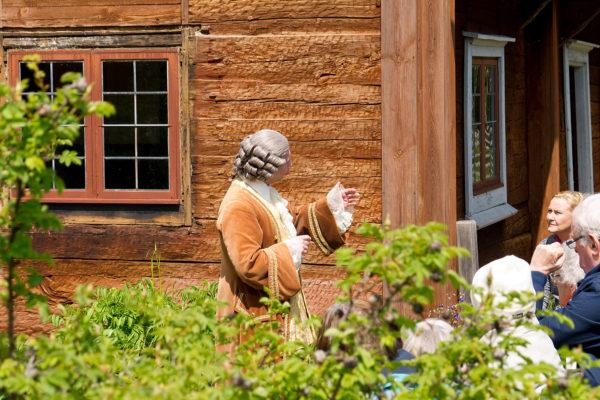 Guidar tur i Linnés Råshult, besökare blir guidad av utklädd man
