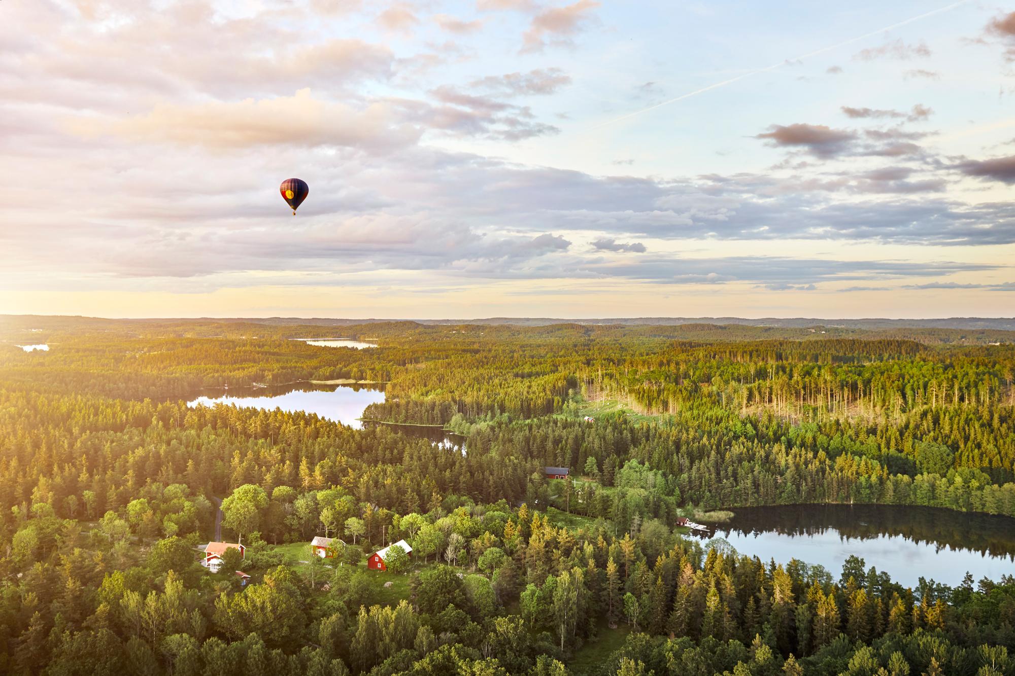 Luftballong i solnedgång över Smålands tusen sjöar och täta granskog, foto av Patrik Svedberg