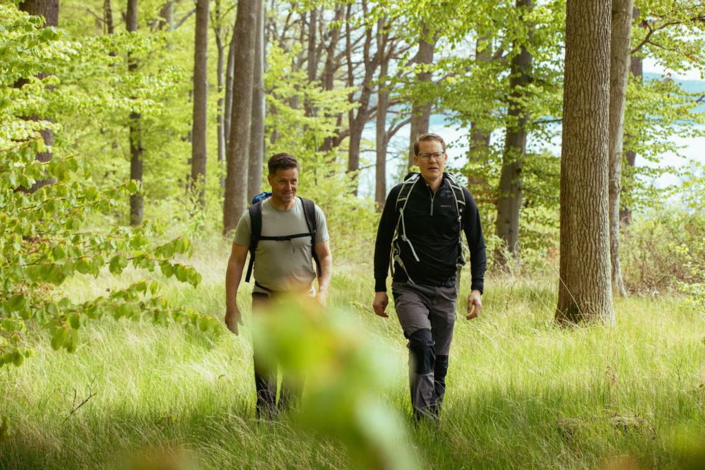 Två män vandrar på John Bauerleden mellan Gränna och Huskvarna, solen skiner