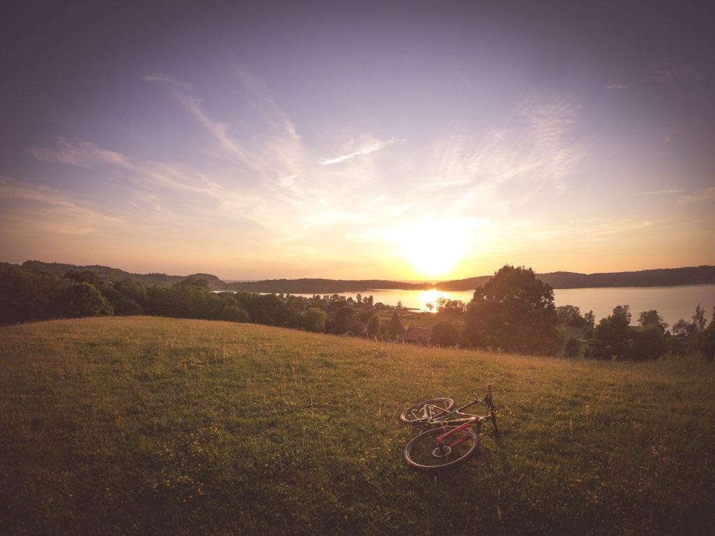 Cykel som ligger ner på fält i solnedgång i Kaxholmen i Småland