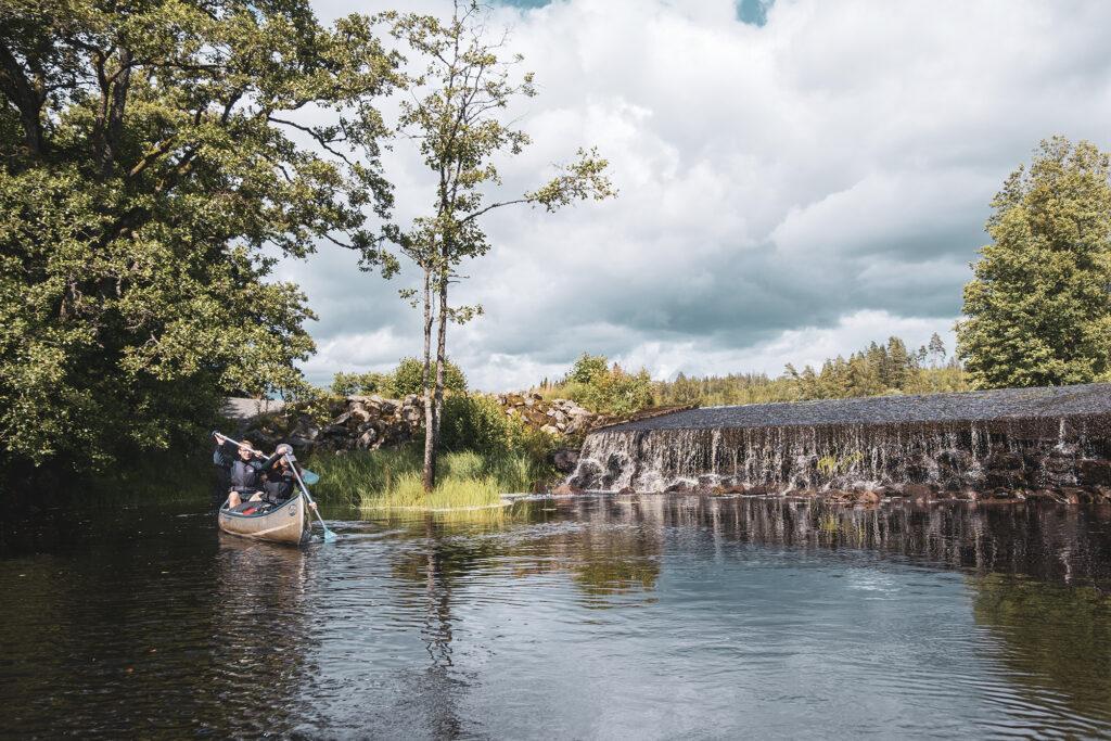 Vid ett vattenfall kommer en kanot flytandes vidare längs ån
