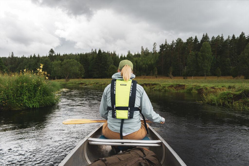 En kvinna med flytväst sitter i en kanot som flyter fram längs en å med öppna ängar vid sidorna och skog längre bort