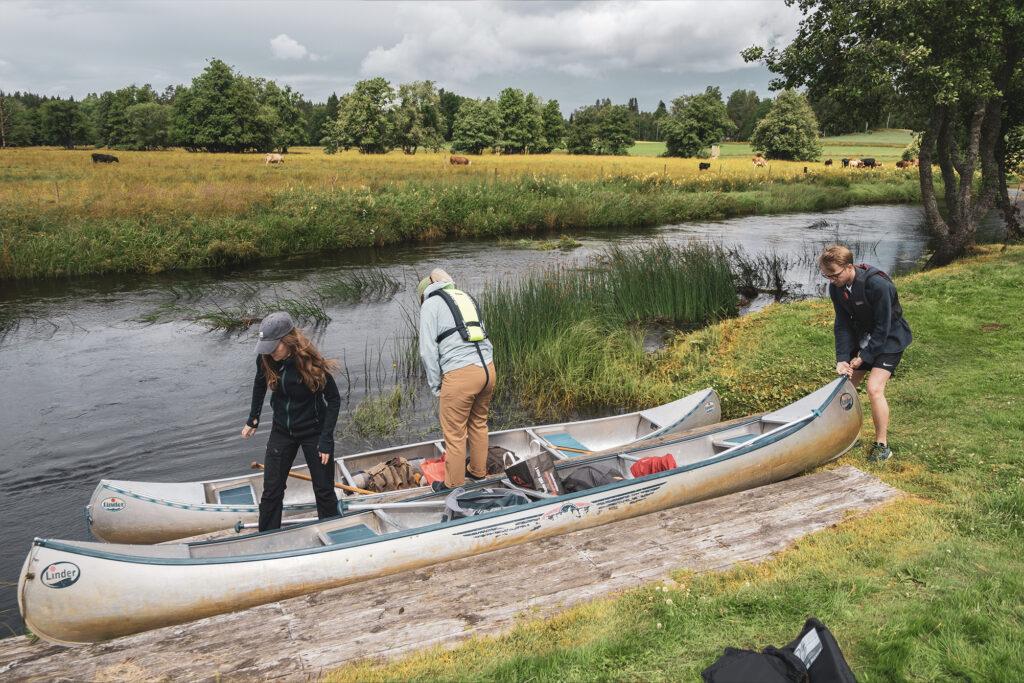 Två kanoter dras ska packas ut och dras upp vid en liten brygga som ligger längst en å med stora ängar i bakgrunden