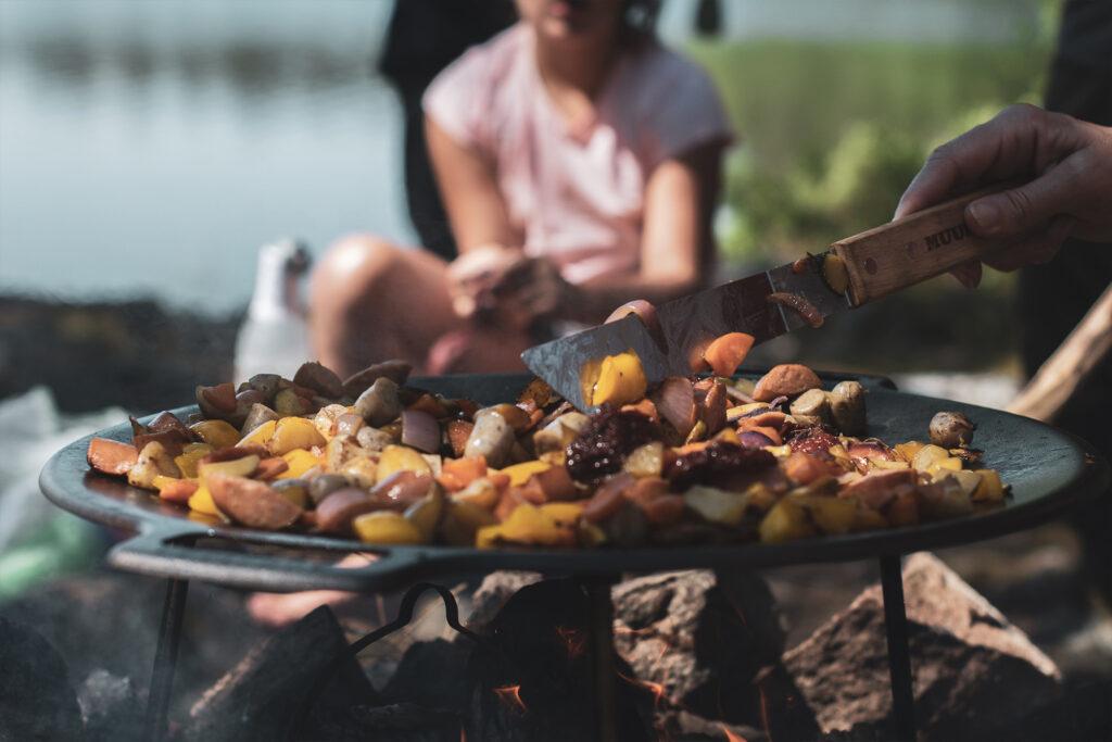 På en vid stekpanna tillagas hackade potatisar, rotfrukter och korv över en öppen eld