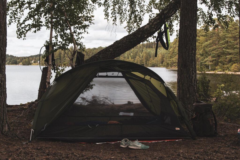 Ett tält står uppslaget vid skogskanten med en sjö precis bakom