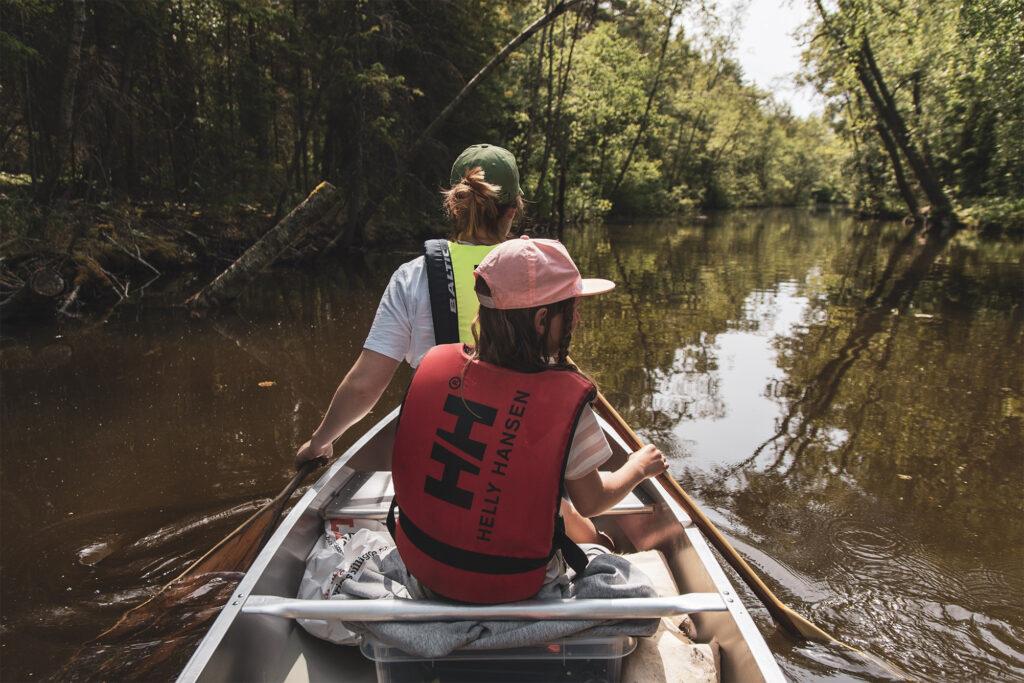 En kvinna och ett barn paddlar kanot på en å med lätt brunt vatten och träd som lutar sig över dom