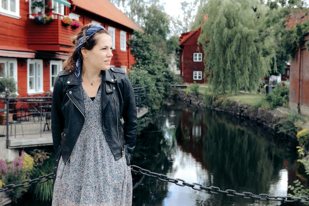 Emma Johansson lutar sig mot ett räcke framför en kanal i den gamla trästaden Eksjö