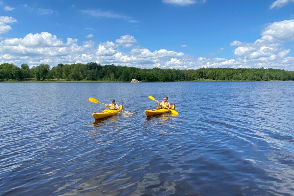 Patrik Widell och hans son paddlar gula kajaker på sjön Åsnen i småland