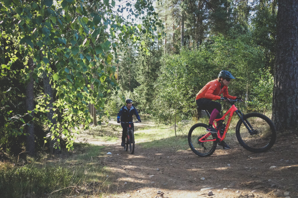 Cycklister cyklar i en skog vid isaberg