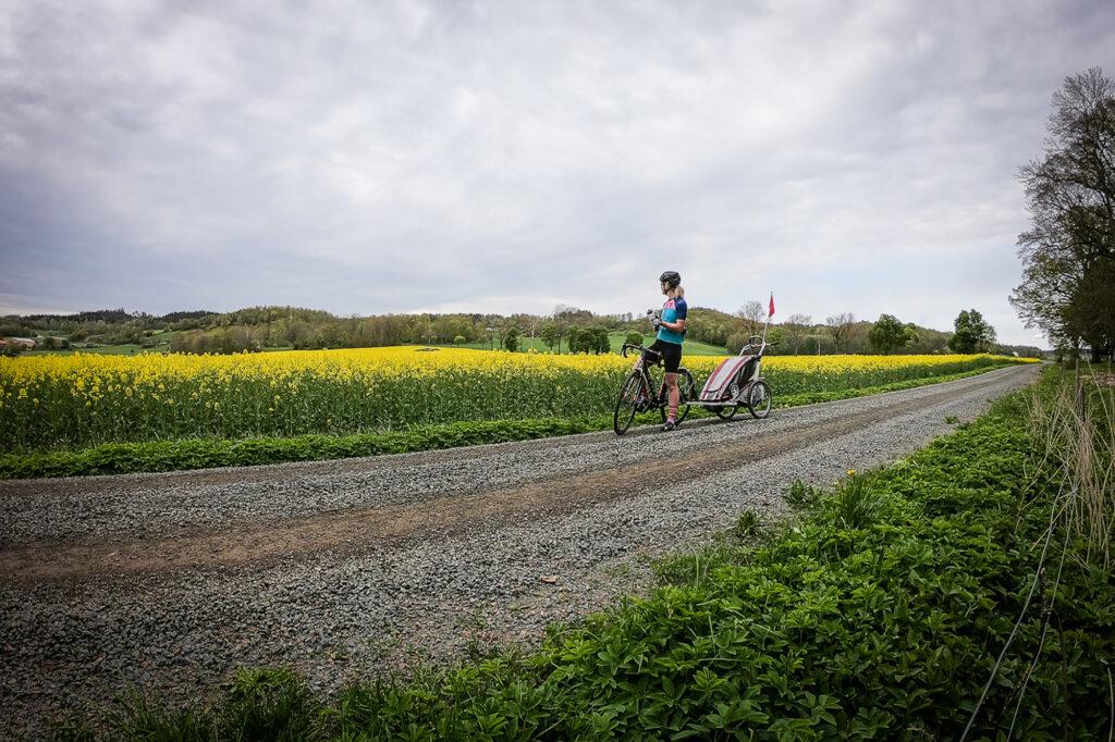 Elna tar en paus i cyklandet bredvid ett rapsfält