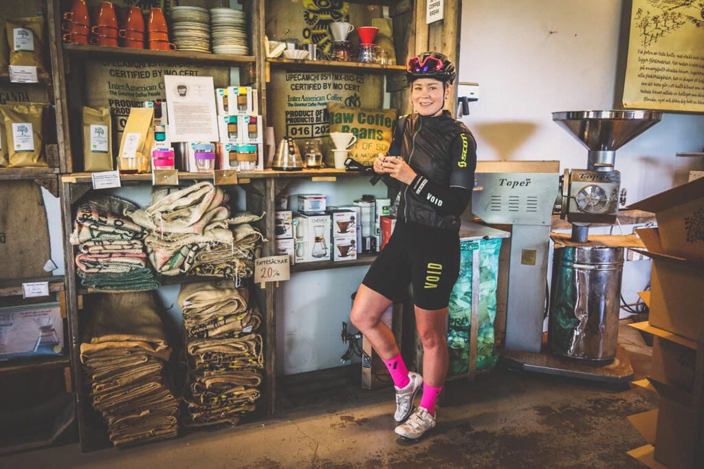 Elna Dahlstrand står på ett cafe i småland med en kopp kaffe i handen i cykelkläder