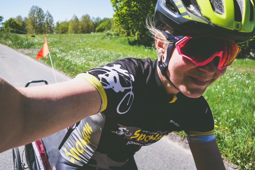 Elna Dahlstrand cyklar leendes fram på en landsväg med en vagn bakom cykeln