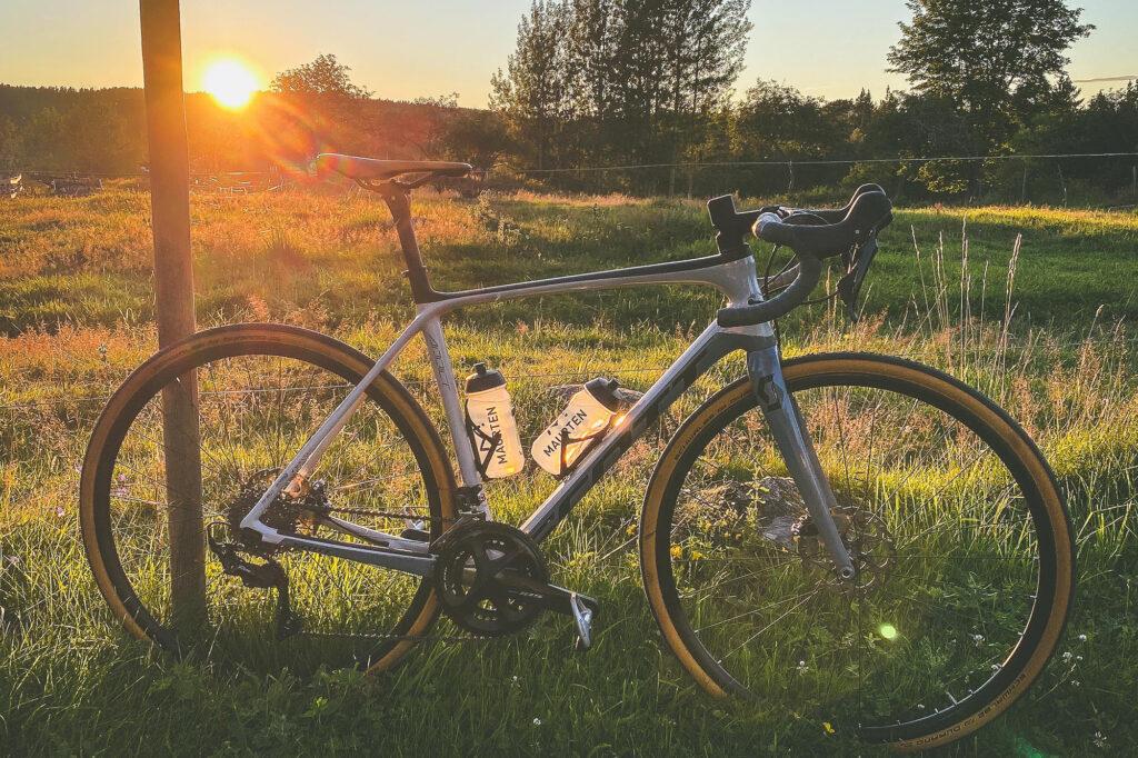 Elna Dahlstrands cykel står lutad mot ett staket vid en äng med en fantastisk solndegång