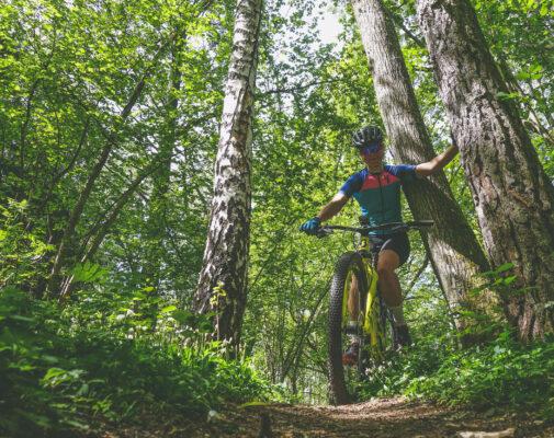 Bild på Elna Dahlstrand cyklandes i skogen.