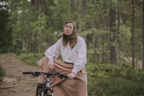 Bild på en sittandes Kristina på en cykel i skogen.