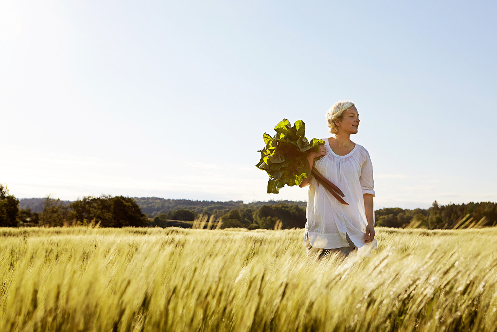 Bild på en kvinna med blommor i handen ute på en äng.