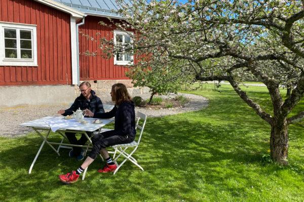 Bild på Mikael och Johan sittandes vid ett fikabord på en grön gräsmatta.